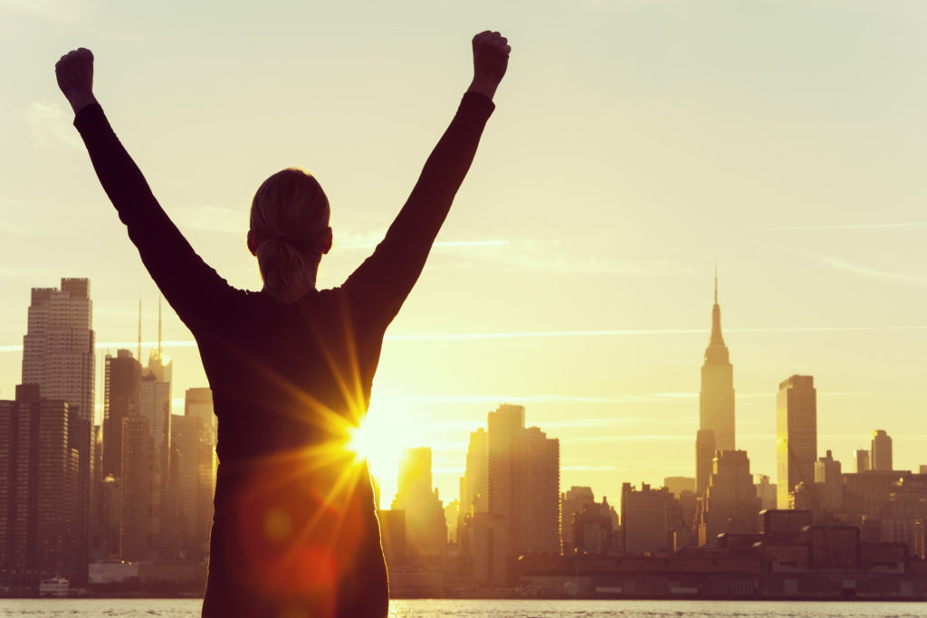 integrity is a part of being success - woman with arms raised infront of NYC skyline